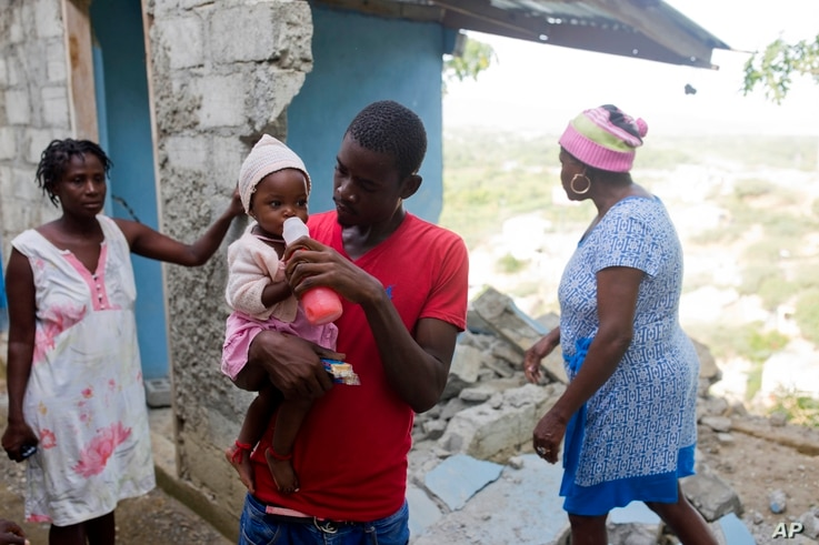 Marc-Sena Docteur feeds his 9-month-old daughter, Size, outside their home damaged in the quake that hit over the weekend in Port-de-Paix, Haiti, Oct. 8, 2018. Docteur's girlfriend died in the earthquake.