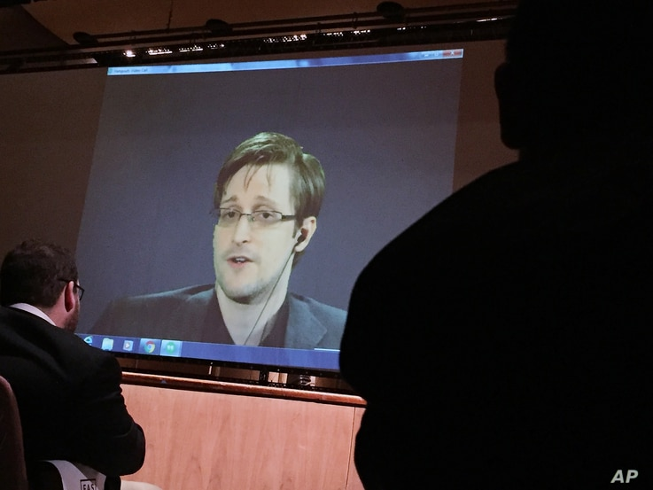 FILE- In this Feb. 17, 2016, photo, former National Security Agency contractor Edward Snowden, center, speaks via video conference to people in the Johns Hopkins University auditorium in Baltimore.
