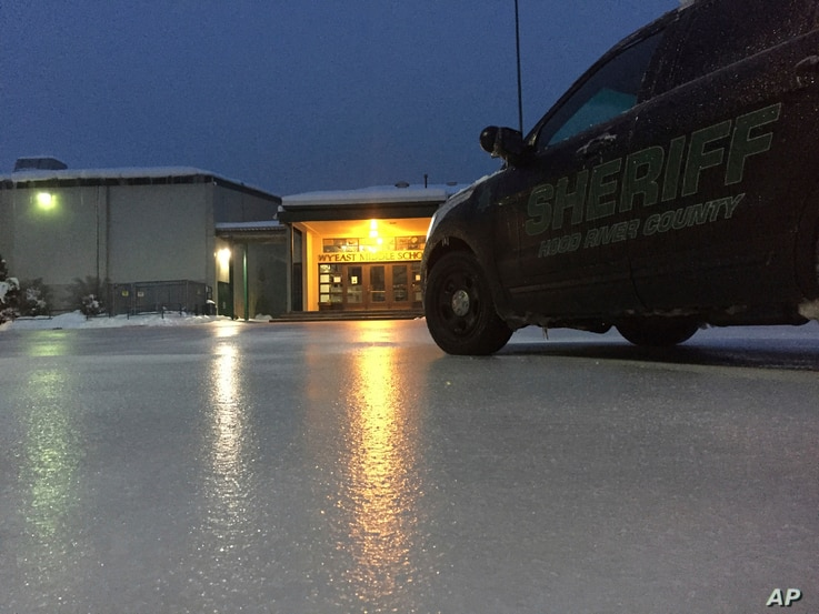 In this image provided by the Hood River County sheriff, lights from a school reflect off the ice-coated parking lot in Hood River, Ore., Jan. 18, 2017.