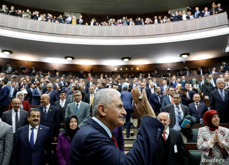 Turkey's Prime Minister Binali Yildirim greets members of parliament from his ruling AK Party as he arrives for a meeting at the Turkish parliament in Ankara, April 18, 2017.