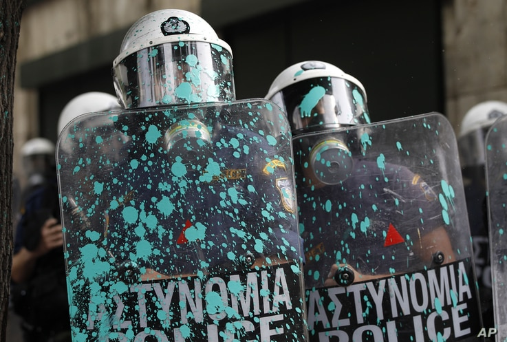 Riot police shields are splattered with paint thrown by protesters during a protest in front of the parliament in Athens, Greece, October 9, 2012.