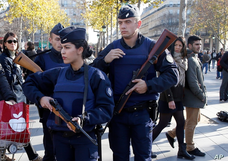 French police patrol at the Monument a la Republique, in the Place de la Republique in Paris, where people are gathering on Nov. 15, 2015, two days after a series of deadly attacks.