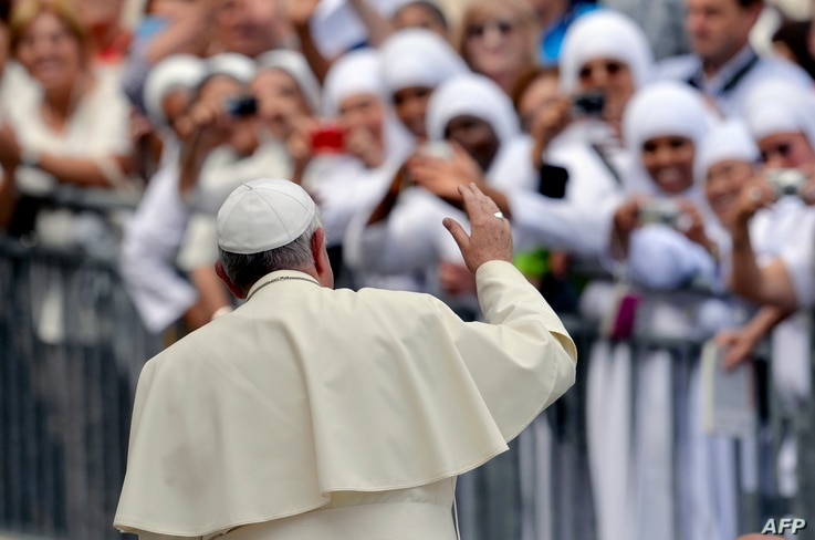 Pope Francis waves to nuns at the end of his weekly general audience in St Peter's square at the Vatican on September 17, 2014.