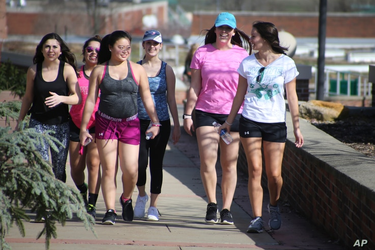 A group of first-year female students at Slippery Rock University smile for the camera as they enjoy temperatures in the 70s on a walk across campus in Slippery Rock, Pa., Feb. 24, 2017.