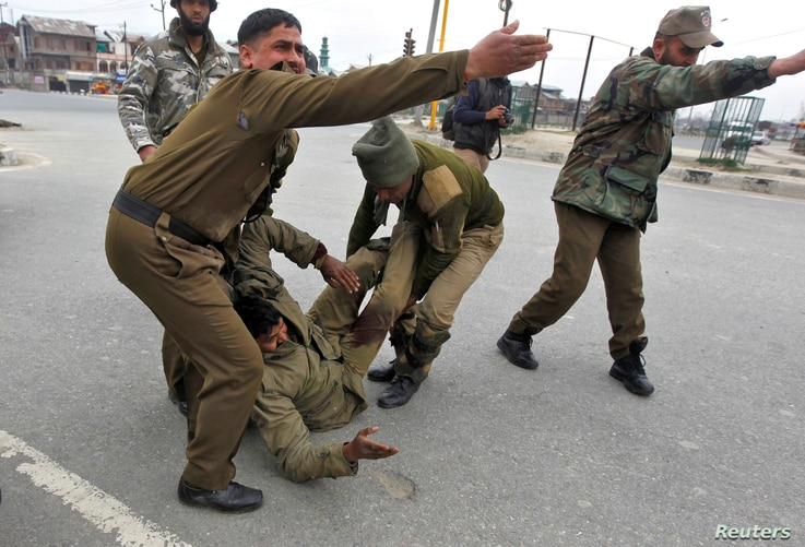 Indian paramilitary soldiers gesture as their wounded colleague lies on the ground during a gunfight in Srinagar, Indian Kashmir, March 13, 2013.