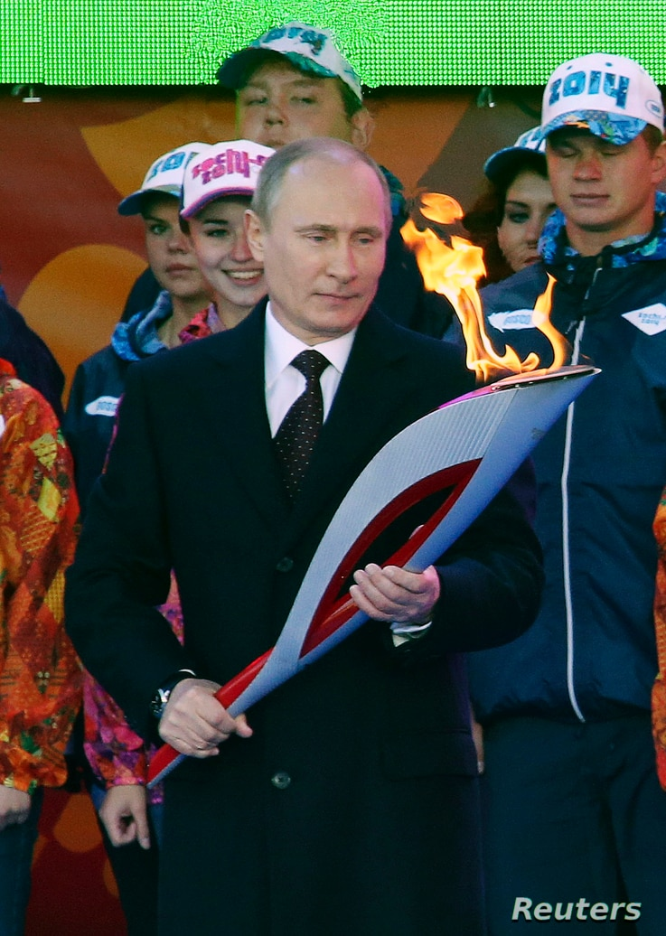 Russian President Vladimir Putin holds a lighted Olympic torch during a ceremony to mark the start of the Sochi 2014 Winter Olympic torch relay in Moscow, Oct. 6, 2013.