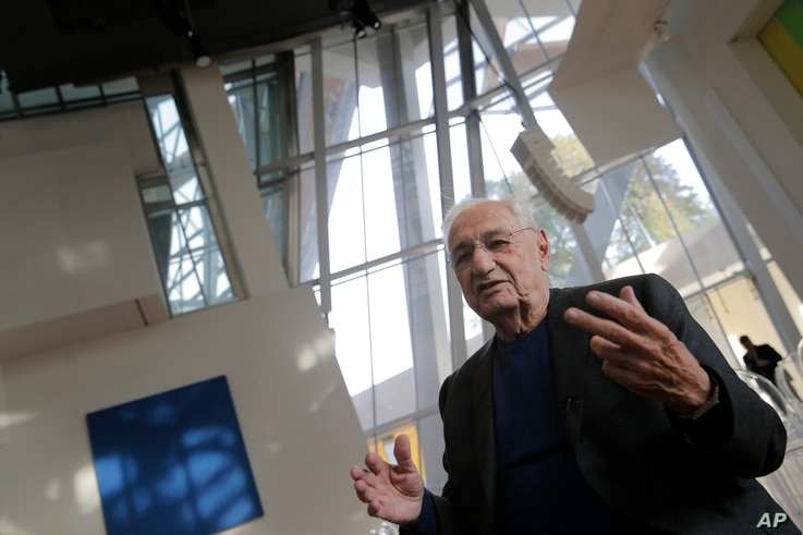 American architect Frank Gehry, center, speaks to journalists  during the press day at his latest creation, the Louis Vuitton Foundation art museum and cultural center, in Paris, Oct. 17, 2014.