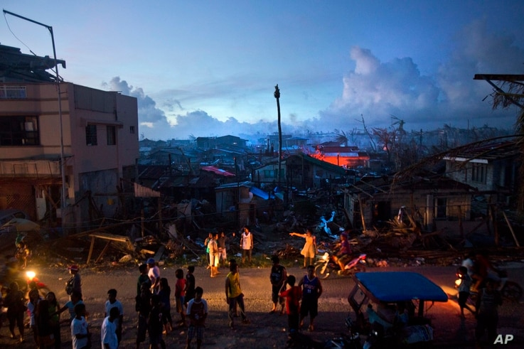 Typhoon Haiyan survivors wait on a roadside in the destroyed town of Guiuan, Philippines on Thursday, Nov. 14, 2013. Typhoon Haiyan, one of the most powerful storms on record, hit the country's eastern seaboard on Friday, destroying tens of thousands