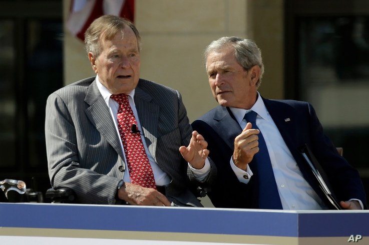 FILE - Former President George W. Bush, right, talks with his father, former President George H.W. Bush, during the dedication of the George W. Bush Presidential Center in Dallas, April 25, 2013. Father and son say they will not be endorsing Donald T...