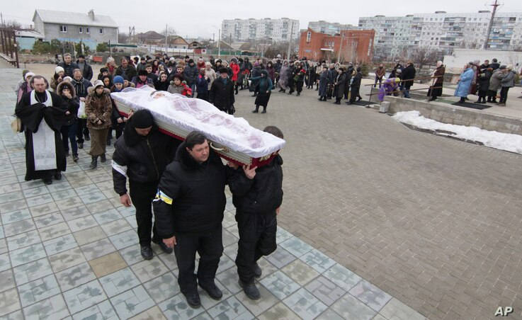 Ukrainians carry a coffin bearing the body of Olga Abdurashitiva, 27, who was killed Saturday during an attack in Mariupol, Ukraine, Jan. 26, 2015.