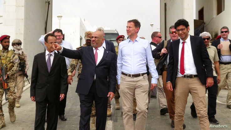 Yemen's Foreign Minister, Khaled al-Yamani, left, walks with British Foreign Secretary, Jeremy Hunt, right, at the presidential palace in Aden, March 3, 2019.