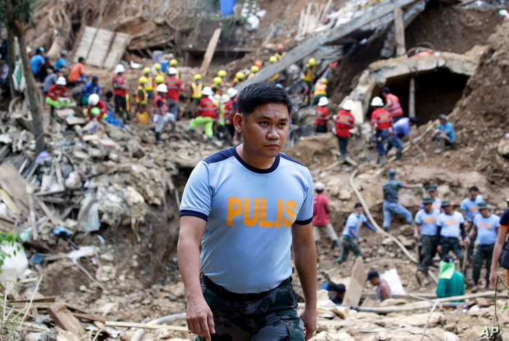 In this Sept. 18, 2018 photo, Philippine Police Senior Inspector Heherson Zambale walks at the site where victims are believed to be buried in a landslide set off by Typhoon Mangkhut as it lashed across Itogon, Benguet province, northern Philippines....