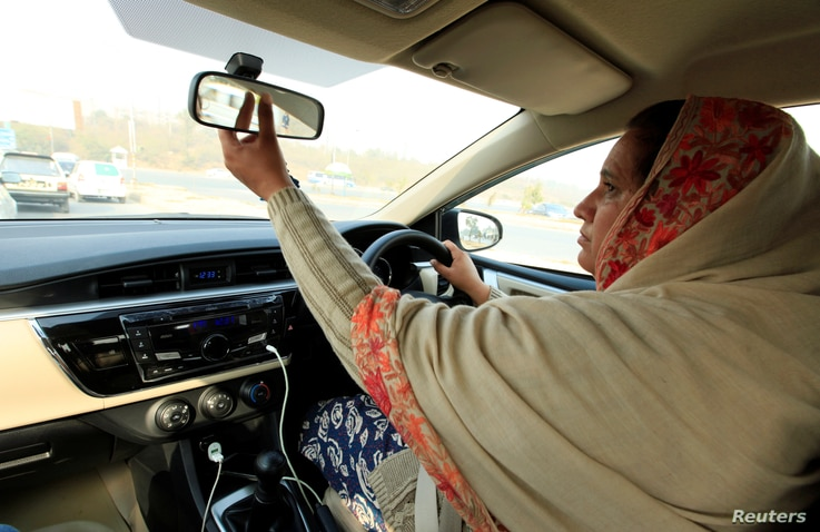 """Yasmin Perveen, one of the pioneer women """"captains"""" of Careem, adjusts her rearview mirror while driving her car in Islamabad, Pakistan, Dec. 7, 2016. In Saudi Arabia, only Saudi men will be allowed to drive Uber or Careem cars."""