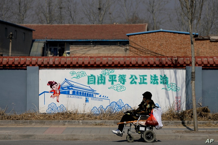 "A Chinese woman in an electric wheelchair passes by traditional government propaganda, with the Chinese words ""Freedom, Equality, Fairness, Rule by Law,"" on the outskirts of Beijing, March 2, 2016."