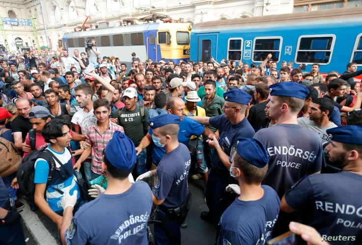 Migrants face Hungarian police in the main Eastern Railway station in Budapest, Hungary, Sept. 1, 2015.