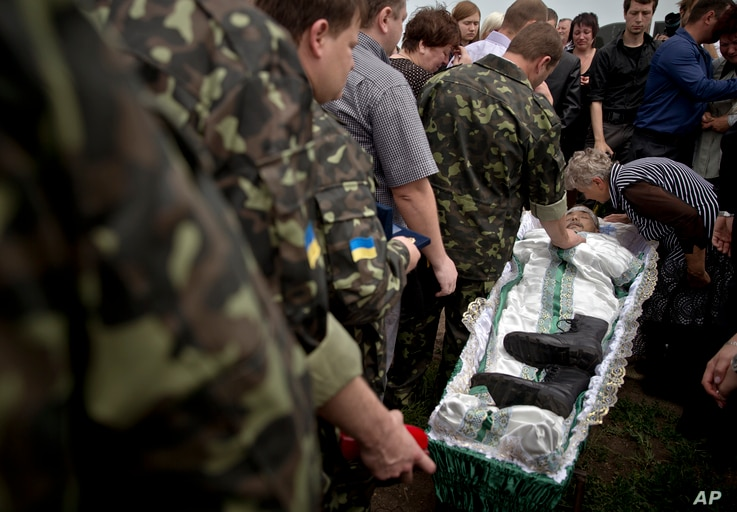 Pro-Russian rebels and relatives walk next to the coffin of Alexander Alexandrovich Gizai, a member of military-patriotic group 'Kaskad' who was killed Monday during clashes with Ukrainian troops, Luhansk, eastern Ukraine, June 4, 2014.