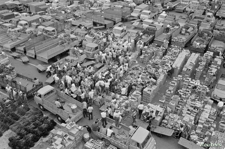 FILE - Wholesalers gather at the Tsukiji market in Tokyo, Japan, in this handout photo taken April 1, 1968 and released by Tokyo Metropolitan Government Office.