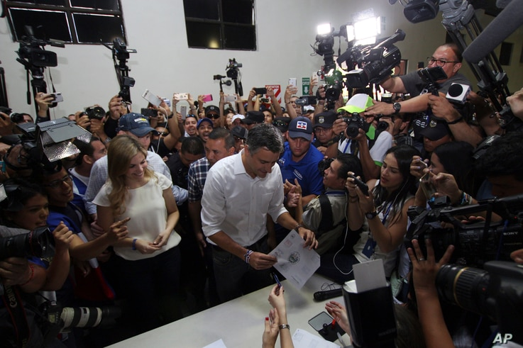 Presidential candidate Carlos Calleja, center, and his wife Andrea vote in presidential elections in San Salvador, El Salvador, Feb. 3, 2019.