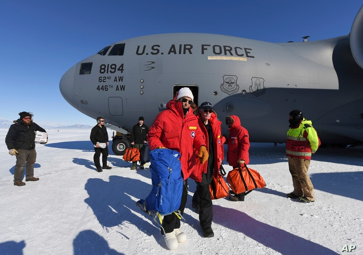 U.S. Secretary of State John Kerry, center, disembarks from a U.S. Air Force C17 Globemaster with the National Science Foundation's Scott Borg, right, at the Pegasus ice runway near McMurdo Station, Antarctica on Nov. 11, 2016.