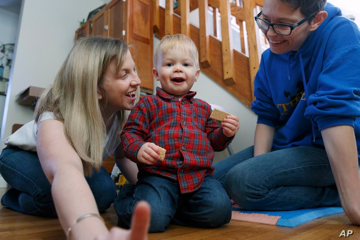 Anna Ford, left, and her partner, Sara Watson, play with their son, Eli, at home in the village of Saunderstown, in Narragansett, R.I., Nov. 16, 2018.
