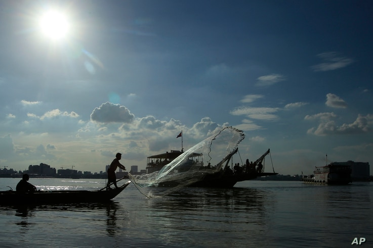 A fisherman casts his fishing net next to a ferry in the Mekong river near Phnom Penh, Cambodia, Tuesday, Dec. 1, 2015.