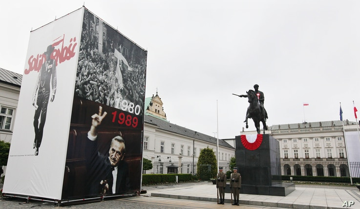 Pictures of Lech Walesa leading the 1980 strike that gave rise to the Solidarity freedom movement, top  and of  Prime Minister Tadeusz Mazowiecki flashing  a v-sign in 1989, bottom on display in front of the Presidential Palace in Warsaw, Poland, Jun...