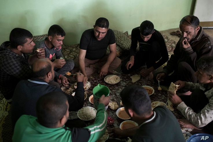 Firas Mohammed al-Jibouri, top right, eats lunch with family members inside his house in Mosul, Iraq, April 5, 2017.