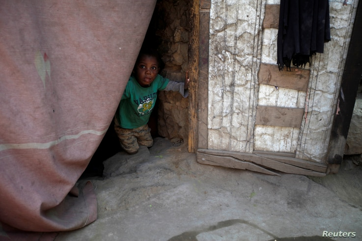 A boy displaced from the Red Sea port city of Hodeida looks from behind a door curtain in a shelter in Sanaa, Yemen, Nov. 2, 2018.