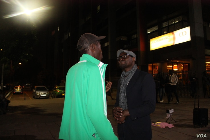 Moses Odhiambo chats with a fan. After his performances, Odhiambo sets aside time to talk with his fans, well-wishers and street kids to talk about his music. (Photo: R. Ombour/VOA)