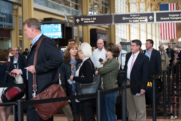 Passengers wait in a security line at Washington's Ronald Reagan National Airport in Washington, May 13, 2016. Fliers across the country have been facing growing lines.