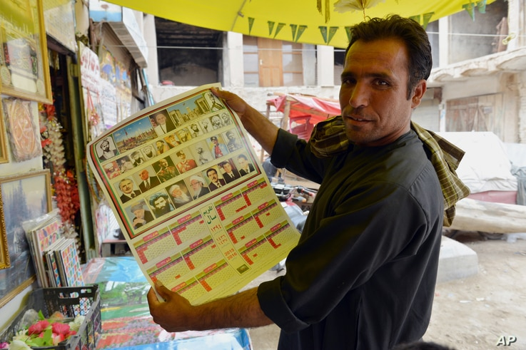 An Afghan store clerk shows a calendar with pictures of Afghan leaders including Mullah Mohammad Omar, bottom row, second left, in Kandahar, south of Kabul, Afghanistan, July 30, 2015.