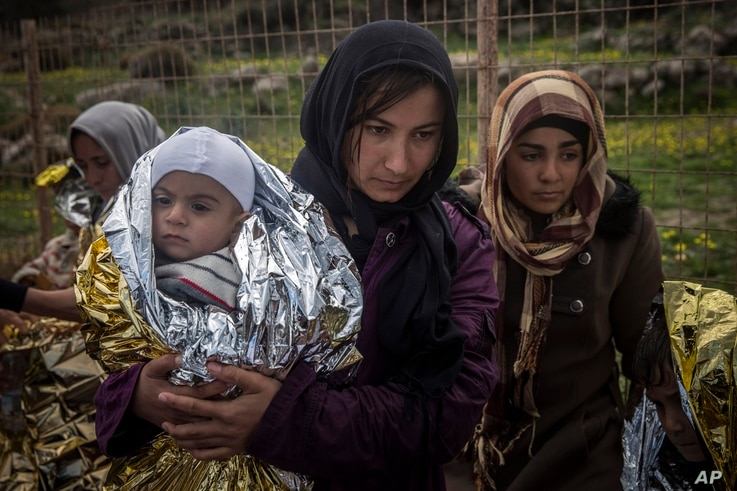 FILE - Women and children stand on a road after their arrival on a dinghy with other refugees and migrants from the Turkish coast to the Greek island of Lesbos, on Wednesday, Nov. 25, 2015.