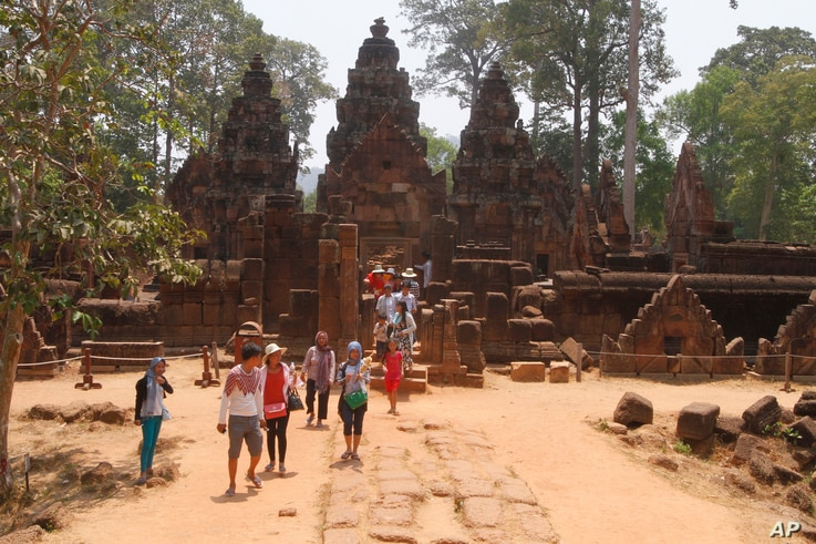 In this April 15, 2016, photo, tourist visit the Banteay Srey temple of the Angkor complex. The Angkor Wat temple is now off-limits to cars as authorities seek to ease traffic jams at the site that draws millions of tourists a year.