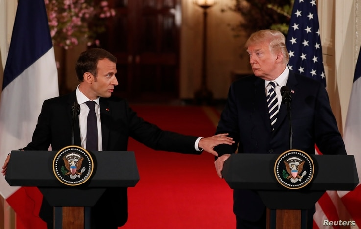 French President Emmanuel Macron reaches out to U.S. President Donald Trump as he speaks during their joint news conference at the White House in Washington, April 24, 2018.