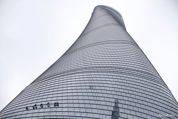 Workers clean the exterior of skyscraper Shanghai Tower at the financial district of Pudong in Shanghai, China, February 23, 2016.