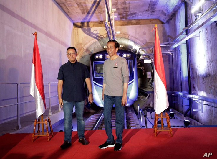"""Indonesian President Joko """"Jokowi"""" Widodo, right, stands on a stage with Jakarta Governor Anies Baswedan with the background of a Jakarta Mass Rapid Transit train during the inauguration ceremony of the subway line system in Jakarta, Indonesia, M..."""