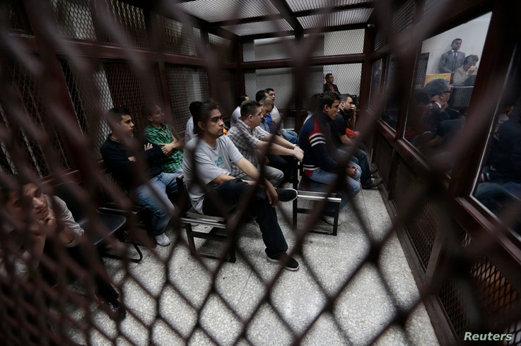 FILE - Members of a gang sit behind bars at a court that deals with gender-based crimes.
