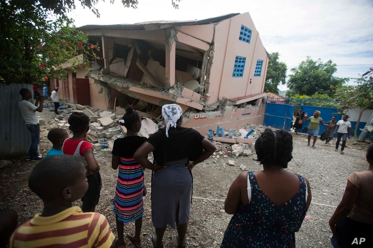 Residents stand looking at a collapsed school damaged by a magnitude 5.9 earthquake the night before, in Gros Morne, Haiti, Oct. 7, 2018.