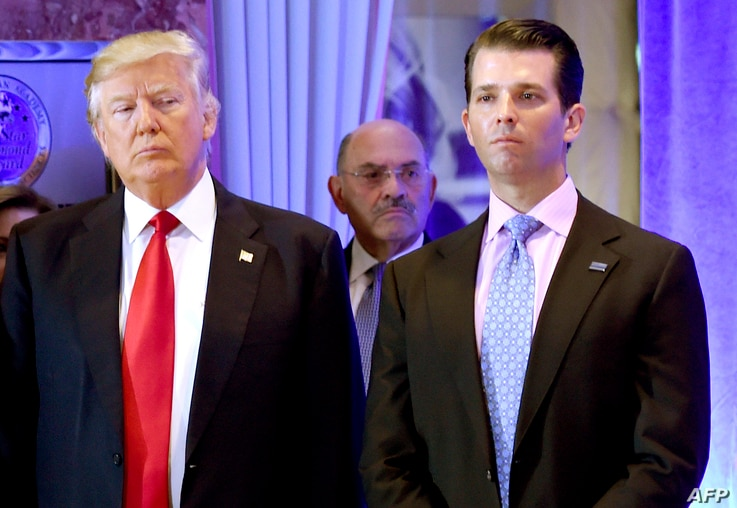 US President-elect Donald Trump along with his son Donald, Jr., arrive for a press conference at Trump Tower in New York, as Allen Weisselberg, chief financial officer of The Trump, looks on.