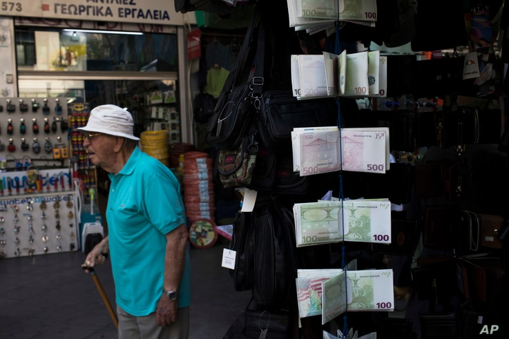 An elderly man walks past wallets designed as euro banknotes, outside a kiosk in central Athens, June 16, 2017. After months of haggling that raised fears of another escalation in Greece's debt crisis, the 19-country eurozone agreed late Thursday to ...