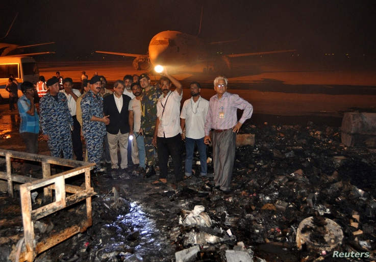 The governor of Sindh province, Ishrat ul Ebad, and security officials visit a damaged area after Sunday's attack on Jinnah International Airport in Karachi, Pakistan, June 9, 2014.