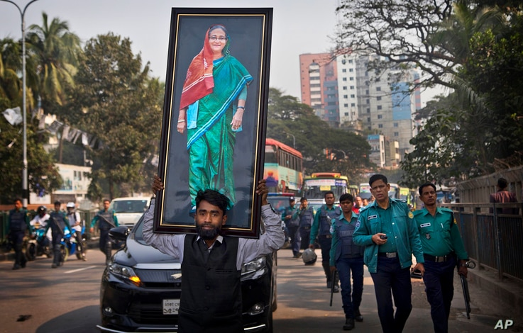 A supporter of Bangladesh Awami League party carries a huge photograph of Bangladesh Prime Minister Sheikh Hasina during an election rally in Dhaka in Bangladesh, Thursday, Dec. 27, 2018.