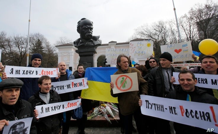 People shout slogans as they stand next to a statue of Ukrainian poet Taras Shevchenko, during a rally against the breakup of the country in Simferopol, Crimea, Ukraine, Sunday, March 9, 2014.