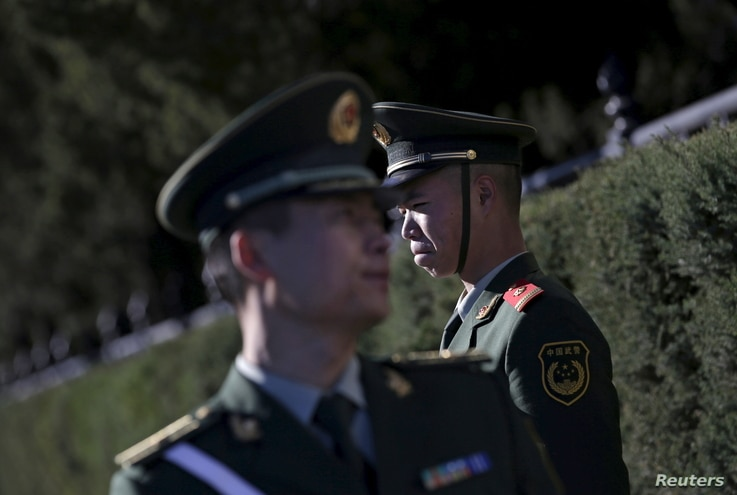 FILE - Paramilitary police officers stand guard for a welcoming ceremony for Germany's Chancellor Angela Merkel outside the Great Hall of the People in Beijing, China. A new report from Amnesty International alleges Chinese police widely use torture....