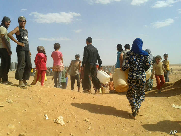 Syrian refugees gather for water at the Rukban camp for displaced Syrians, on the Jordan and Syria borders, June 23, 2016.
