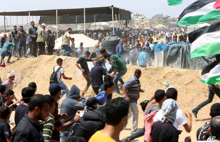 Palestinian protesters run for cover from teargas fired by Israeli troops near the Israeli border fence, east of Khan Younis, in the Gaza Strip, May 14, 2018.