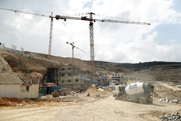 Workers and buldozers working at a construction site in the Israeli settlement of Givat Zeev near the West Bank city of Ramallah, April 14, 2016..