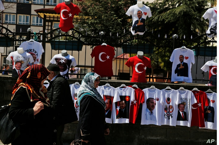 People walk past a display of T-shirts adorned with images of the Turkish flag and President Recep Tayyip Erdogan, offered for sale in his hometown city of Rize, April 4, 2017, ahead of an April 16 referendum on extending presidential powers.