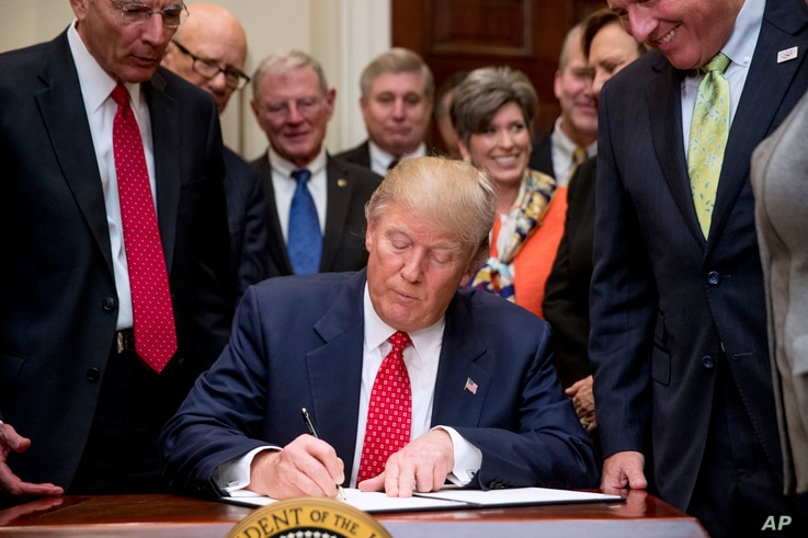 President Donald Trump signs the Waters of the United States (WOTUS) executive order, Feb. 28, 2017, in the Roosevelt Room in the White House in Washington.