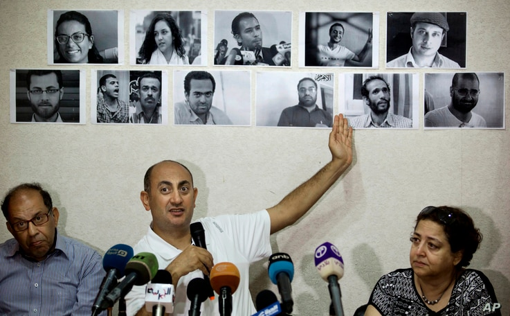 FILE - Egyptian lawyer and former presidential candidate Khaled Ali points to photos of jailed activists, who were arrested during protests over two disputed Red Sea islands, including Egyptian rights lawyer Malek Adly, top row third right, during a ...